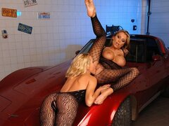 A couple of fishnet wearing hotties lick and caress each other on the hood of a corvette