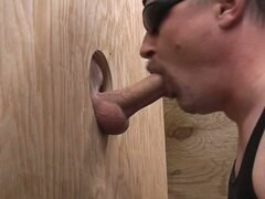 Horny gay dude sucks big cock through a hole