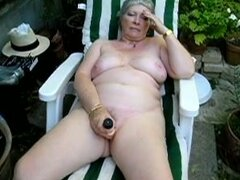 Chuby mature slut dildo fucks snatch on the beach chair