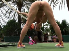 Indecent behavior of naked sporty girl on the green tennis court