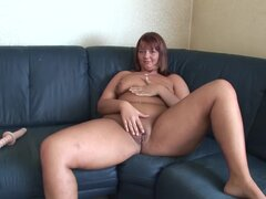 Busty Redheaded Euro MILF toys both holes on her couch