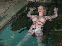 Busty girl bound and submerged in water outdoors