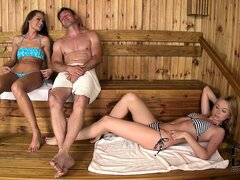 Two sexy slim babes seduce a young stud in the sauna to satisfy their desires