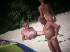 Voyeur on the beach capturing a tanned and naked girl
