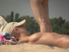 The naked body of beach nudist girl stretched on the sand