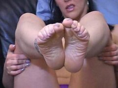 Masturbation instructor raises her feet up and starts stroking it together like she is performing a footjob on a mans cock