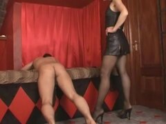 Leather mistress gives over the knee spanking