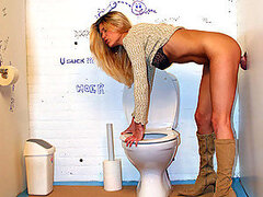 A beautiful blonde babe is interrupted having a pee by a cock through the wall