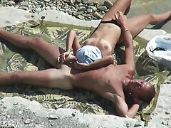 A naked couple lay on a nudist beach and ever so gently play with each other's bits