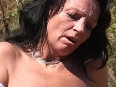 Mature milf with big tits plays with a huge dildo outdoors