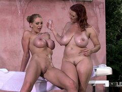 Two stacked babes with oiled up bodies drive their cunts to climax with a dildo