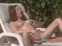 Hot brunette is sunbathing and rubbing and toying her pussy
