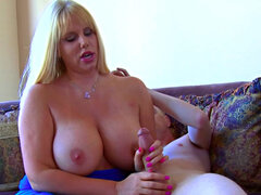 Blonde milf with amazing tits gives a handjob on the sofa