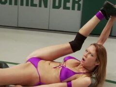 Two naked chicks wrestle on the mat and then fuck each other