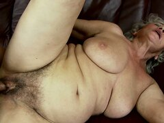 A busty mature babe lies on the sofa and a young stud fucks her hairy pussy