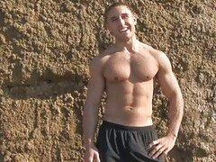 Muscular gay dude strips on the beach