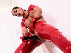 Wild brunette in red latex suit exposes her big tits and drills her cunt with a dildo