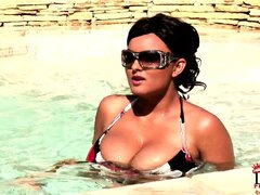 Babes with massive juggs let them loose to take a dip in the pool