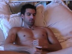 Muscular solo gay with huge hands is masturbating his cock on the bed