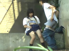 Sweet Asian student is sitting out on the steps with her boyfriend