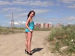 Beauty lifts her aqua dress outdoors