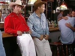 Two hot cowbays drinking beer in a gay bar