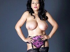 Handsome busty burnette with garter belt and stockings poses