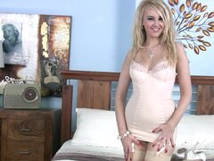 Sexy blonde Katie Kay undressing herself in a bedroom