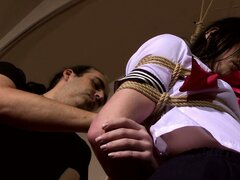Cute babe in a schoolgirl outfit gets strung up in rope bondage
